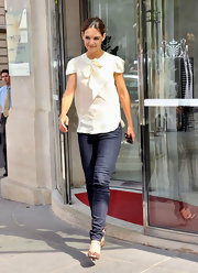 Katie looked sweet and summery in a cream tie neck blouse and blue jeans at the Dior boutique.