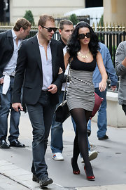 "Katy wears big oval ""Karmic"" shades in black with a vintage grey lens to match her dress and tights."