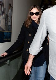 Keira Knightley caught a flight at LAX looking chic in black cateye sunnies.
