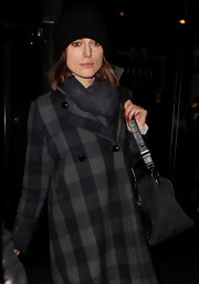 Keira Knightley bundled up at the airport in a black cable-knit beanie.