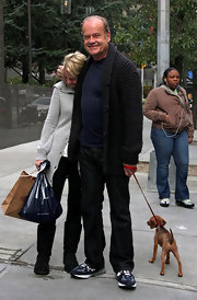 Kelsey Grammer walked his dog wearing a black cardigan over a tee, jeans, and running shoes.