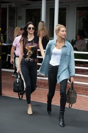 Hailey Baldwin layered an oversized denim shirt over a tight white tank top for a day out with pal Kendall Jenner.