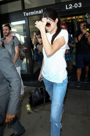 Kendall Jenner injected some edgy elegance into her airport look with a black Valentino Rockstud tote.