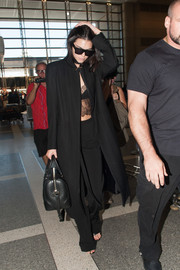 Kendall Jenner was a head turner at LAX in a black Ann Demeulemeester coat teamed with a Sharon Wauchob lace crop-top and Sally LaPointe pants.