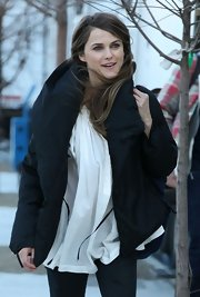 Keri Russell bundled up on stage in this black puffy jacket over a blousy white shirt.