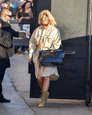 Khloe Kardashian matched her coat with beige lace-up boots by Yeezy.