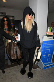 Khloe Kardashian teamed her hoodie with ripped black jeans.