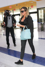 Khloe Kardashian caught a flight wearing a black moto jacket over a tight top.