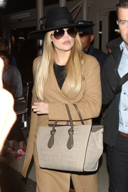 Khloe Kardashian tried to keep a low profile at LAX with a wide-brimmed hat by Maison Michel.