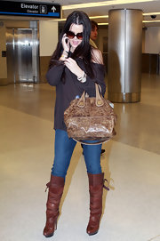 "Khloe's knee-high  brown leather boots feature a wrapped strap detail and a 1"" platform for extra comfort."
