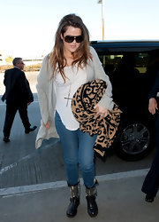 Khloe accessorized her travel style with black flat boots complete with embellished detailing.