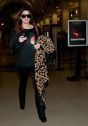 Khloe topped off her look with ruched black knee-high boots.