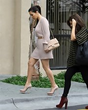 Kim Kardashian completed her neutral ensemble with this tan quilted bag for her business meeting.