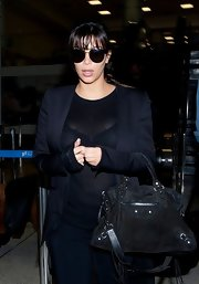Kim Kardashian stuck to a classic black handbag while traveling.