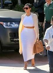 Kim Kardashian accentuated those curvy hips with a tight white Wolford maxi skirt (which was actually a dress worn as a skirt).