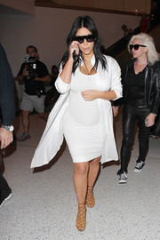 A white shirtdress over Kim's maternity outfit added a more sophisticated touch.
