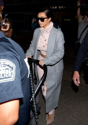 Kim Kardashian arrived at LAX rocking a tattered pink turtleneck crop-top and matching leggings by Chanel.