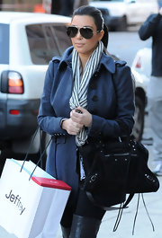 Kim Kardashian never leaves the house without looking stylish. She rocked a navy pea coat and matching scarf, which she paired with a suede shoulder bag.