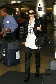 "At the airport, Kim goes with a modern black version of the ""Insider"" with a gradient black lens with red tones."