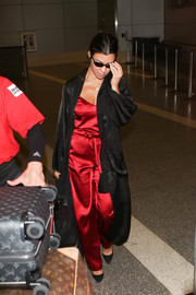 Kourtney Kardashian topped off her boudoir-inspired airport look with a black silk duster by Love x Labels.