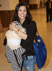 New mommy Kourtney Kardashian is seen arriving at Miami airport with baby. She managed to stay stylish by carrying a a cool blue leather chain strap bag.