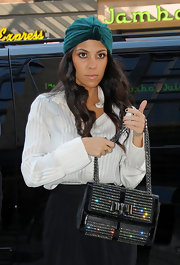 Kourtney looked the part of a NYC socialite in a emerald green head wrap and a gleaming Sweet Charity shoulder bag.