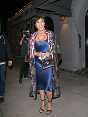 Kris Jenner matched her dress with a pair of navy ankle-strap sandals.