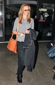 Lisa Kudrow's orange leather messenger bag looked perfect for traveling.