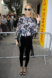 Poppy Delevingne arrived for the Topshop Unique fashion show wearing a long-sleeve braid-print blouse.