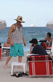 This isn't the Adam Lambert that we're all used too... no black eye shadow or spikey hair on the beach!  Adam sports a straw hat and tank top.