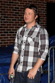 Jamie is a big fan of plaid, here he wears a white and brown pocketed button-up.