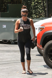 Lea Michele teamed her top with black capri leggings.