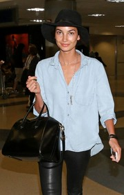 Lily Aldridge topped off her travel outfit with a floppy black suede hat.
