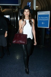 Lily Aldridge went for an edgy travel look with a white tank top teamed with black leather skinnies.