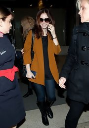 Lily Collins opted for a burned orange wool coat for her travel look while flying to LAX.