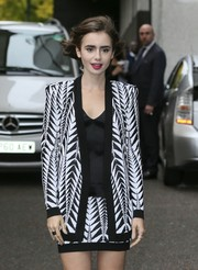 Lily Collins wore a matching two-piece Balmain skirt suit featuring a monochrome pattern leaving London's ITV Studios.