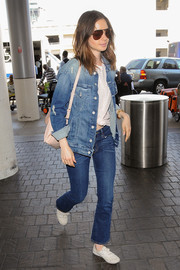 Lily Collins went for a rugged airport look with this ripped denim jacket by Mother.