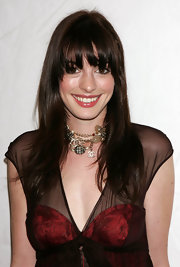 Anne Hathaway wore a charm choker necklace with her cocktail dress for the Luca Luca fashion show.