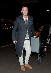 Luke Evans traveled in style with a classic gray wool coat and t-shirt.