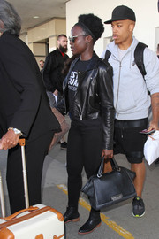 Lupita Nyong'o sealed off her airport look with flat black boots.