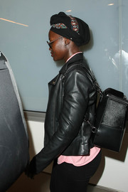 Lupita Nyong'o caught a flight carrying a boxy black backpack.
