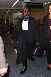 Lupita Nyong'o looked airport chic in her long navy duster coat with button details that she paired over a neutral look while making her way through LAX.