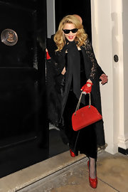 Madonna accented her black dress with several pops of red, including a posh red patent chain strap purse.