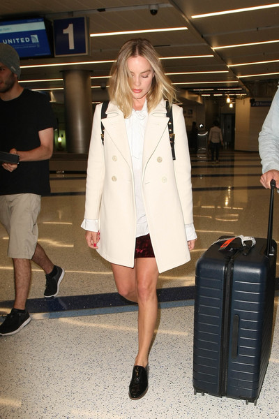 Margot Robbie teamed black patent slip-ons by Louise et Cie with a cream-colored pea coat for a flight.