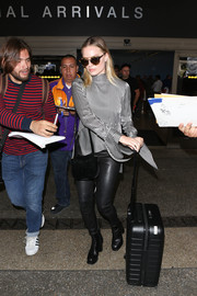 Margot Robbie landed at LAX looking stylish in a high-neck striped blouse and leather skinnies.