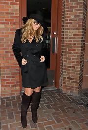Mariah Carey was a woman of mystery in a timeless black trenchcoat and a matching fedora.