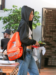 Miley Cyrus was spotted out carrying a bright orange backpack by Moschino.