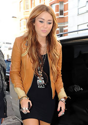 Miley Cyrus added a little edge to her sexy black dress with a tan leather jacket.
