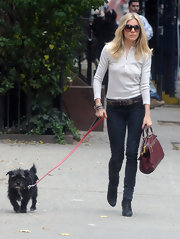 Sienna carries a red leather tote with gold trim while walking her dog.