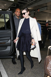 Miranda Kerr donned a simple navy crewneck sweater for a flight to LAX.